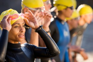 Swimmers ready for a race with hats, goggles and wetsuits.