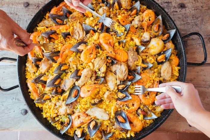 Mixed paella and hands with forks taking rice. Aerial view.